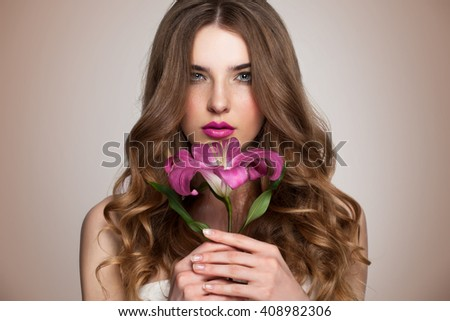 Young beautiful healthy blond girl with pink flower on brown background. - stock photo