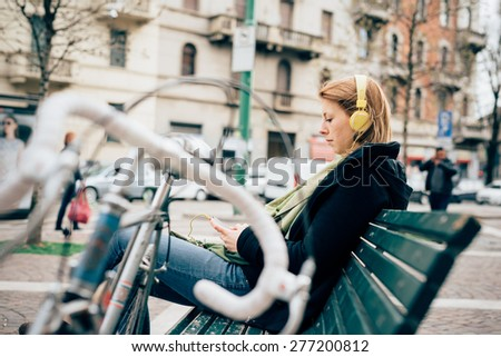 young beautiful hipster sporty blonde woman in town with bike and headphones - stock photo