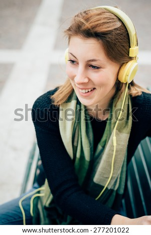 young beautiful hipster sporty blonde woman in town with headphones smiling