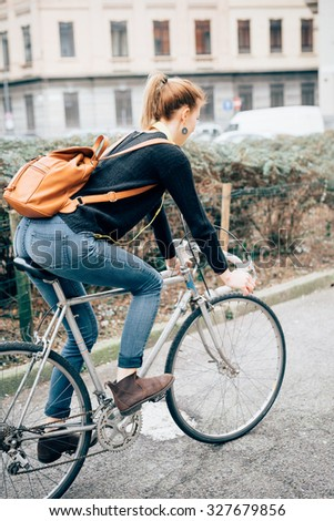 young beautiful hipster sporty blonde woman, view from back, riding her bike in the street - sportive, healthy, alternative methods of transportation concept