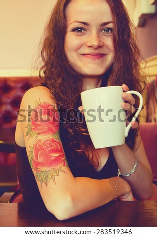 young beautiful hipster tattooed  woman with red curly hair at the bar with cup of coffee. Vintage style picture - stock photo