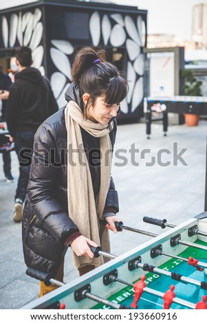 young beautiful hipster woman playing table football in the city - stock photo