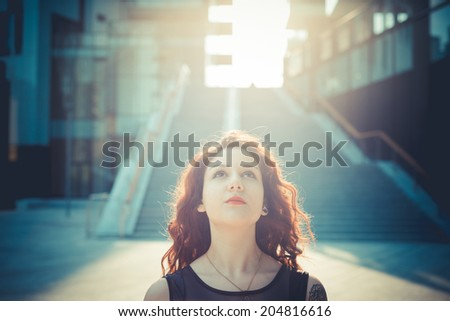 young beautiful hipster woman with red curly hair in the city - stock photo