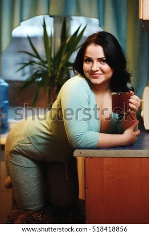 Young beautiful housewife drinking tea in kitchen