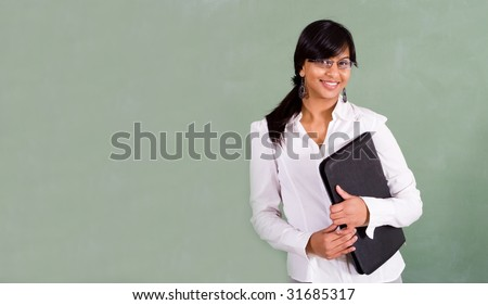 young beautiful indian school teacher standing in front of blackboard - stock photo