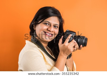 Young beautiful indian woman taking a photo with a digital camera, asian girl with camera, indian girl holding dslr camera, camera and lady, Portrait of a cheerful indian woman making photo on camera - stock photo
