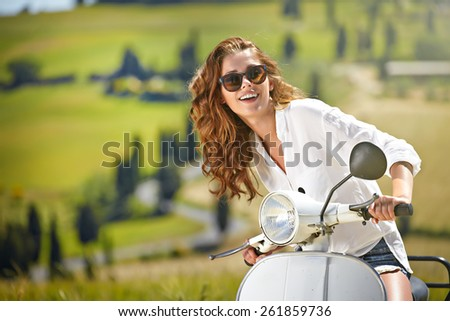 Young beautiful italian woman sitting on a italian scooter in Italy hills - stock photo