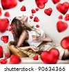 Young beautiful lady drinking champagne on valentine day cute red hearts are flying around her. - stock photo