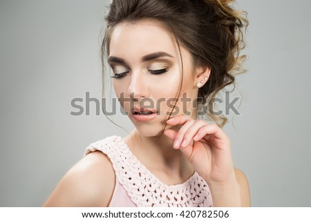 Young beautiful lady in tender pink dress posing in studio on grey background. not isolated.Supple wedding make up hairstyle and neutral lips.Gorgeous spring portrait. Charming face, close up - stock photo
