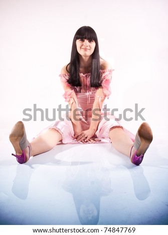 Young beautiful lady is sitting on floor in pink dress