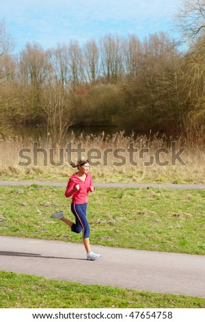 Young beautiful lady jogging in a park. - stock photo