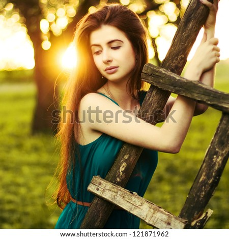 Young beautiful lady posing in apple garden. Spring portrait lit by warm evening light. - stock photo