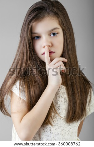 Young beautiful Little girl  has put forefinger to lips as sign of silence - stock photo