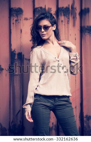 young beautiful long hair woman portrait with sunglasses , outdoor in the city, wearing shirt and pants in front of rusty metal background - stock photo