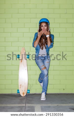 young beautiful long-haired brunette girl in blue helmet with wooden longboard skateboard coquettishly sending an air kiss near the green brick wall - stock photo