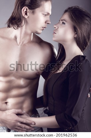 Young beautiful loving couple is embracing on a dark background