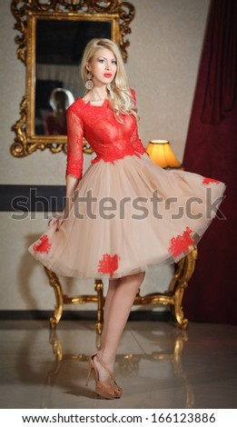 Young beautiful luxurious woman in elegant dress. Beautiful young blonde woman with a mirror in background. Seductive blonde woman in luxury manor, vintage style - stock photo