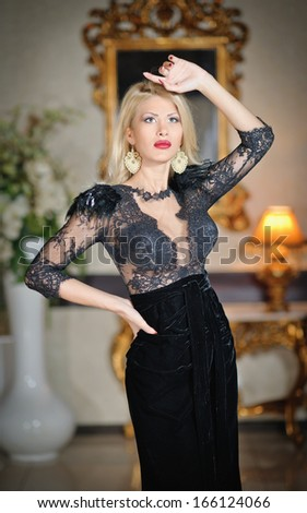 Young beautiful luxurious woman in long elegant black dress. Beautiful young blonde woman with a mirror in background. Seductive blonde woman in luxury manor, vintage style - stock photo