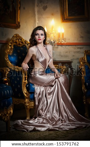 Young beautiful luxurious woman in long elegant dress .Beautiful young woman in a luxurious classic interior. Seductive brunette woman in luxury manor, vintage style - stock photo