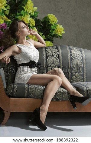 Young beautiful luxurious woman sitting on a vintage couch - stock photo