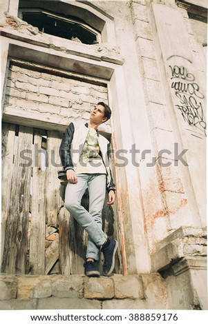 Young beautiful man in a jacket, jeans and sneakers standing outdoors. stylish fashion portrait