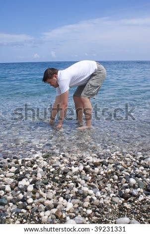 Young beautiful man washing his hands in the sea .