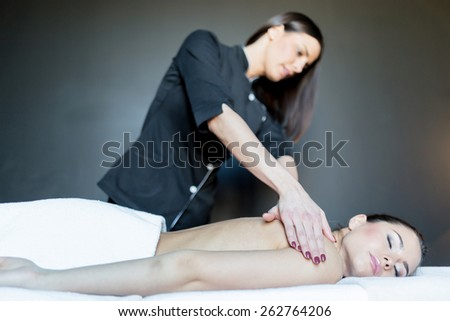 Young, beautiful massage therapist massaging a stunning young lady laying with her lying on her chest - stock photo