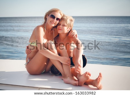 young beautiful mather with son by the boat  - stock photo
