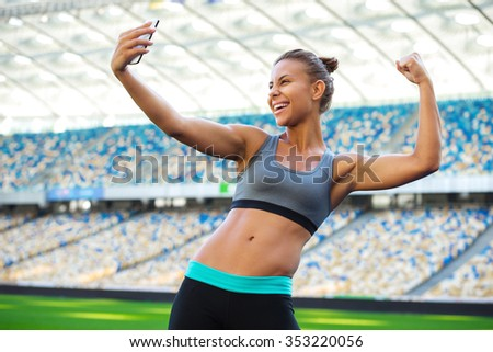 Young beautiful mixed race sportswoman making selfie photo on mobile phone after training outdoors and smiling. Fit woman is at large nice modern stadium - stock photo