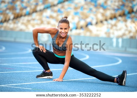 Young beautiful mixed race sportswoman stretching outdoors and smiling. Fit woman is at large nice modern stadium