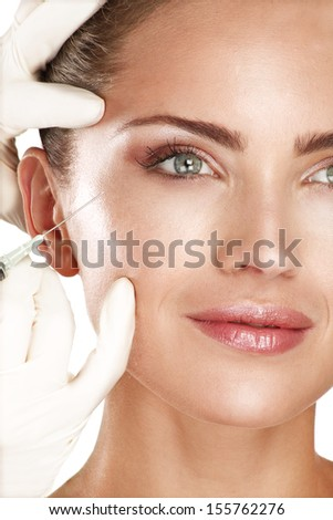 young beautiful model injecting  a cosmetic treatment  on white - stock photo