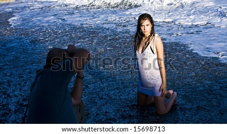 Young beautiful model posing wet on the beach - stock photo