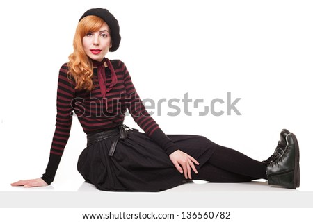 young beautiful model with a beret and a skirt sitting on an edge of a platform isolated on white background - stock photo