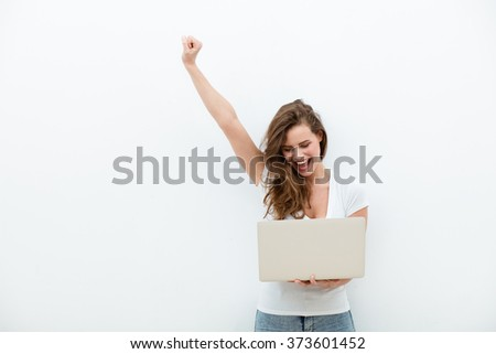 young beautiful modern woman having an laptop in hands, leaning on a white wall, happy - stock photo