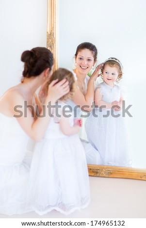 Young beautiful mother and her adorable curly toddler daughter wearing white dresses standing in front of a big mirror - stock photo