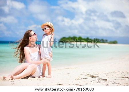 Young beautiful mother and her adorable little daughter at tropical beach