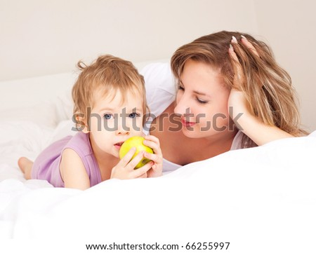 young beautiful mother and her baby on the bed at home - stock photo