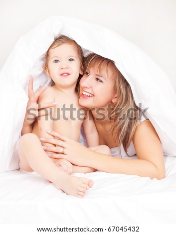 young beautiful mother and her baby on the bed at home after the shower (focus on the baby) - stock photo