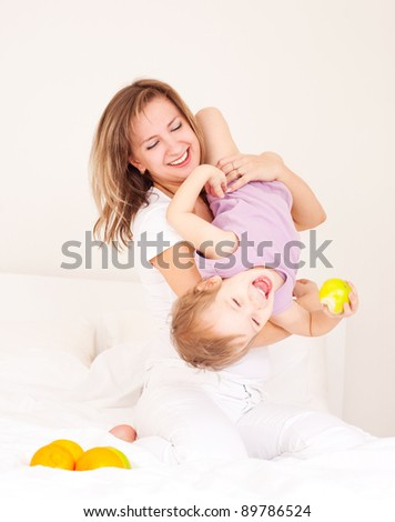 young beautiful mother and her baby with fruit on the bed at home (focus on the woman)
