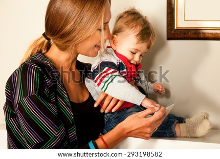 Young beautiful mother and her cute  little boy are looking and playing with a smartfone indoors. Copy space frame. - stock photo