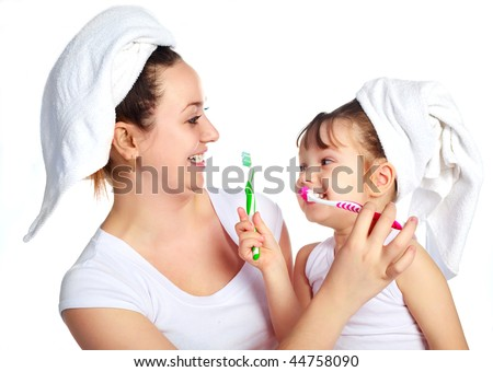 young beautiful mother and her little daughter brushing teeth and laughing - stock photo