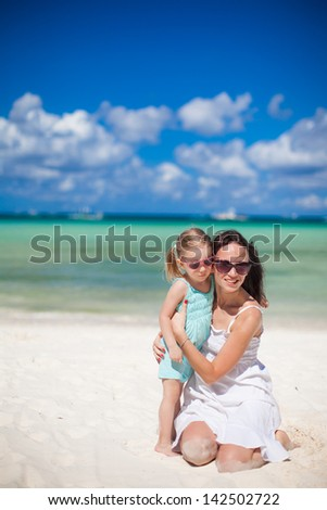 Young beautiful mother and her little daughter on white beach