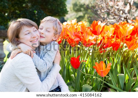 young beautiful mother and her little son hugging and celebrating mother's day by the blooming flowers in the park at springtime - stock photo
