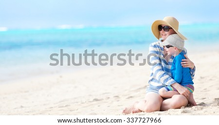 young beautiful mother and her son sitting together at the beach and enjoying summer vacation together - stock photo