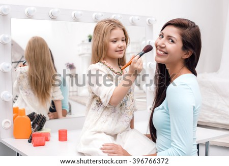 Young beautiful mother and little daughter while applying makeup. Nice cozy bedroom. Daughter helping mother to use brush for makeup - stock photo