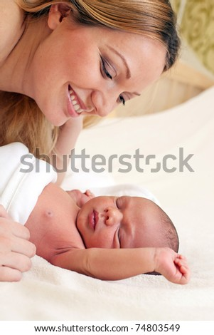 Young beautiful mother and newborn baby boy - stock photo