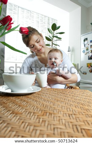 young beautiful mother feeding her little cute baby daughter at the kitchen - stock photo