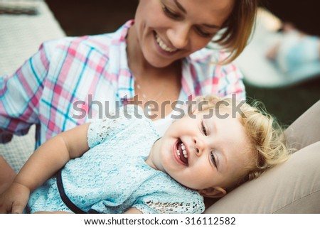 Young beautiful mother has fun with her daughter during a walk outdoors. Toned image - stock photo