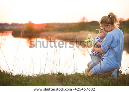 Young beautiful mother hugging her little toddler son on a sunset in a wild flowers field near lake. Happy woman with her baby boy on a summer sunny day. Family walking by the river. Lifestyle concept - stock photo
