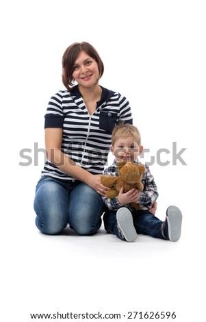 Young beautiful mother in blue jeans sitting with her son three years on the floor in the studio, isolate on white.